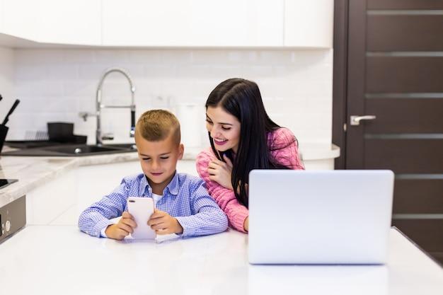 Jovem mulher usando um computador portátil para trabalhar em casa enquanto seu filho jogando jogos no telefone. jovem ocupada trabalhando no laptop. Foto gratuita