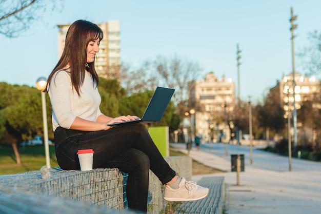 Jovem mulher usando um laptop na rua. conceito de trabalho freelance. Foto Premium