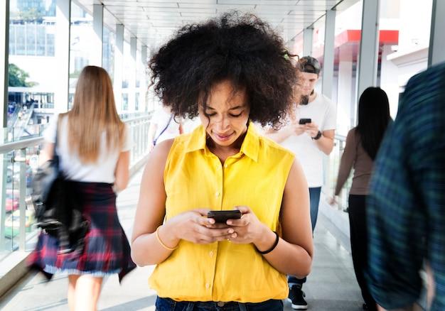 Jovem, mulher, usando um smartphone no meio da multidão andando Foto Premium