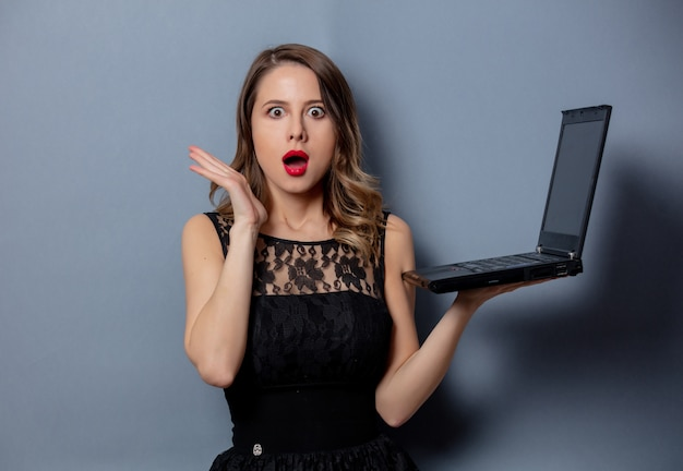 Jovem mulher vestida de preto com notebook na parede cinza Foto Premium
