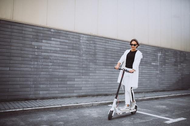 Jovem mulher vestida de scooter de equitação branca Foto gratuita