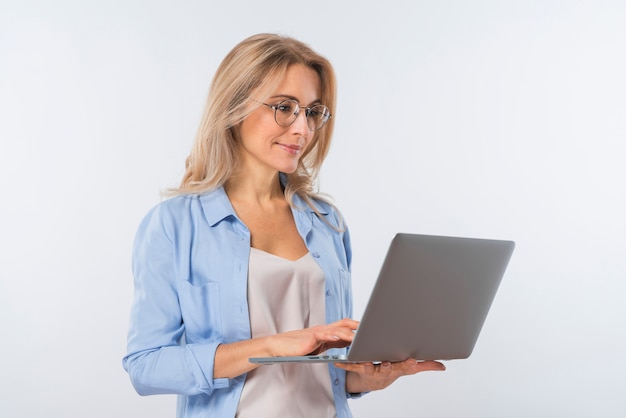 Jovem mulher vestindo óculos usando laptop contra fundo branco Foto gratuita