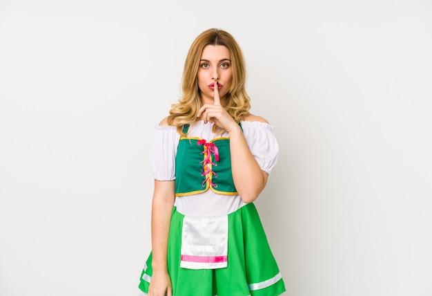 Jovem mulher vestindo uma roupa de saint patricks day isolada, mantendo um segredo ou pedindo silêncio. Foto Premium