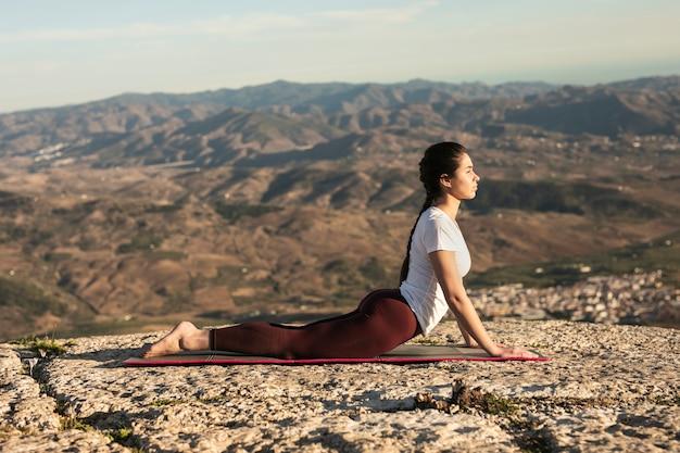 Jovem mulher vista frontal na esteira praticando ioga Foto gratuita