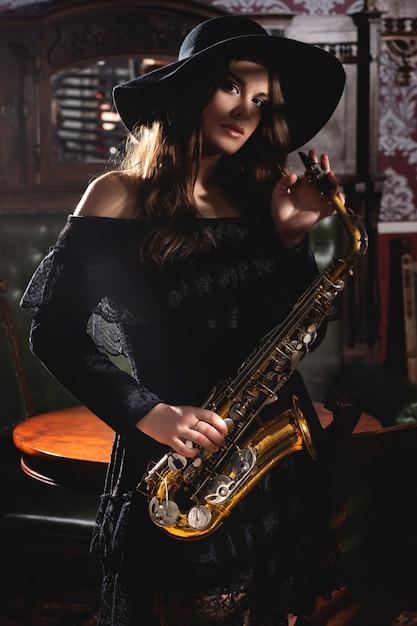 Jovem músico atraente com um saxofone Foto Premium