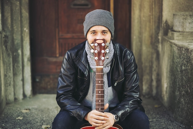 Jovem músico com guitarra na cidade Foto gratuita