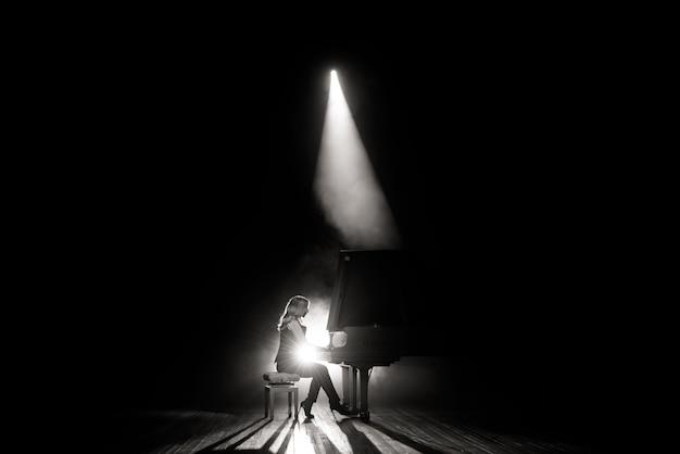 Jovem músico tocando o piano de cauda no palco Foto Premium