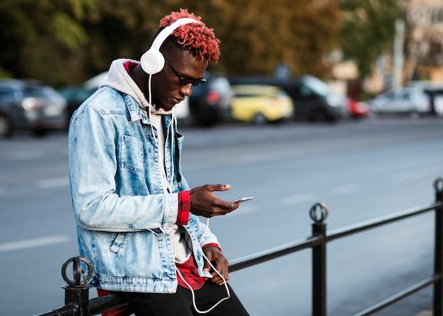 Jovem na cidade, olhando para o telefone Foto gratuita