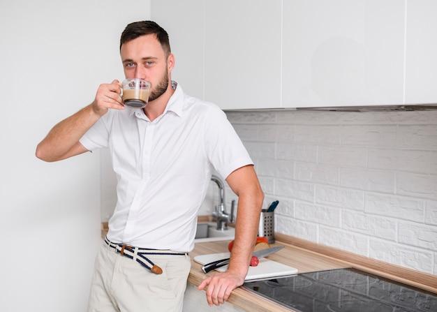 Jovem na cozinha, desfrutando de um café Foto gratuita