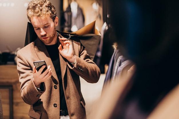 Jovem na loja de moda masculina, falando ao telefone Foto gratuita