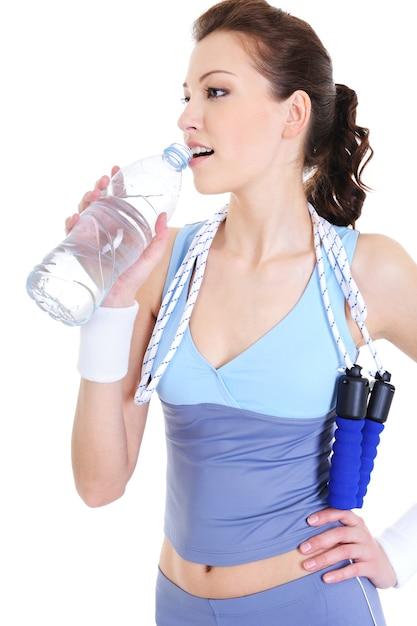 Jovem na recreação do treinamento bebendo água Foto gratuita