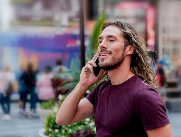 Jovem na rua falando por telefone Foto gratuita