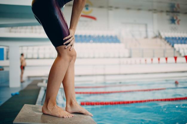 Jovem nadador se preparando para a competição e nadar na piscina Foto Premium