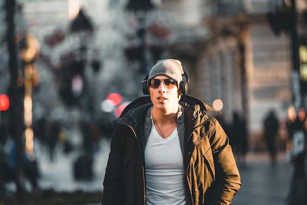 Jovem nas ruas da cidade de inverno com fones de ouvido Foto Premium