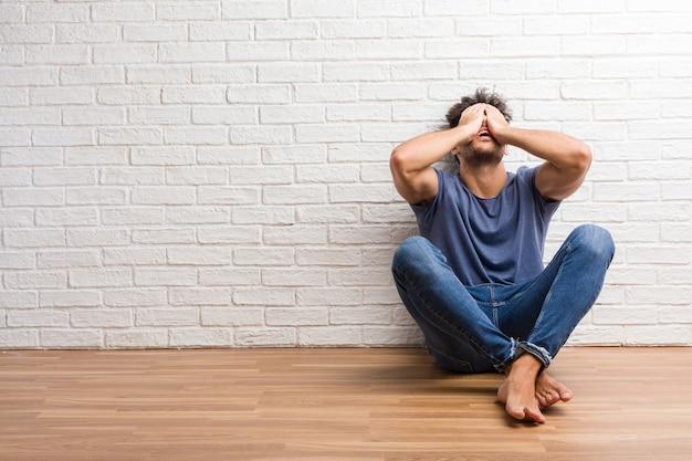 Jovem natural sente-se num chão de madeira frustrado e desesperado, irritado e triste com as mãos na cabeça Foto Premium