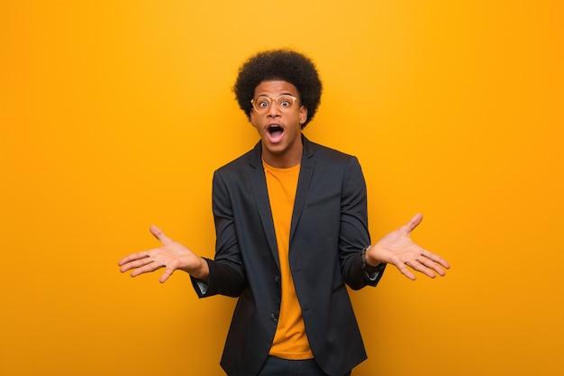 Jovem, negócio, homem americano africano, sobre, um, laranja, parede, celebrando, um, vitória, ou, sucesso Foto Premium