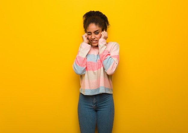 Jovem negra americana africano com olhos azuis, cobrindo as orelhas com as mãos Foto Premium