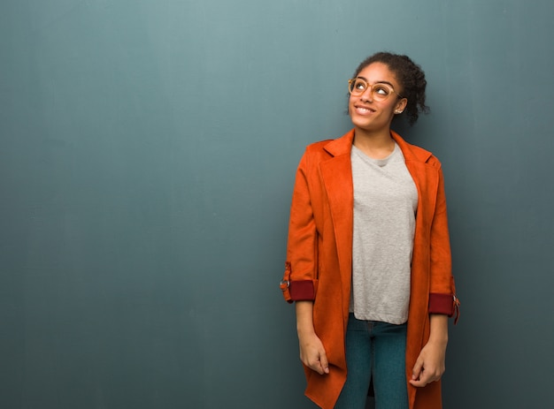 Jovem negra americana africano com olhos azuis sonhando em alcançar objetivos e finalidades Foto Premium