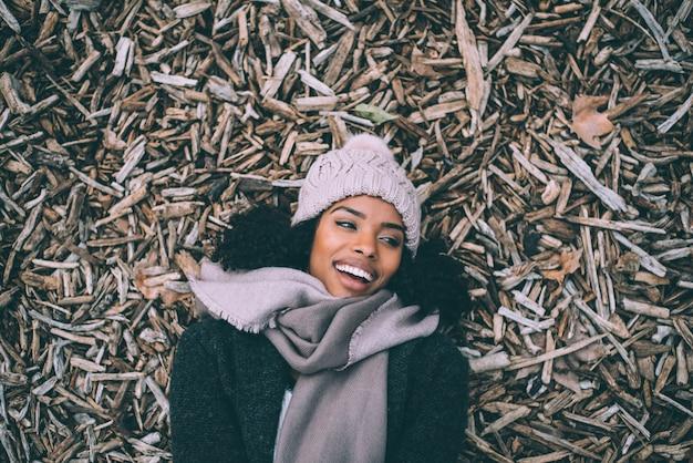 Jovem negra linda deitada em pedaços de madeira Foto Premium