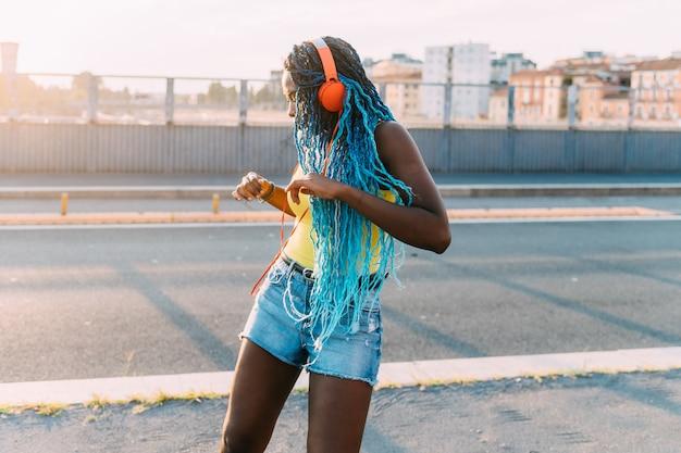 Jovem negra mulher milenar ao ar livre escutando música dançando Foto Premium