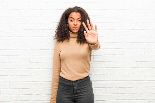 Jovem negra olhando sério mostrando a palma da mão aberta, fazendo o gesto de parada contra a parede de tijolos Foto Premium