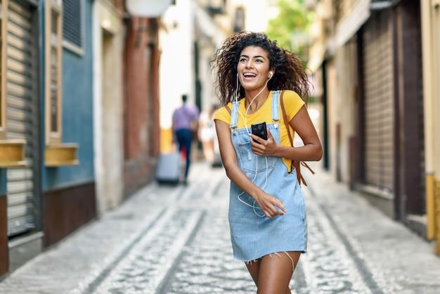 Jovem negra ouvindo música com fones de ouvido ao ar livre Foto Premium
