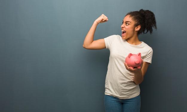 Jovem negra que não se rende ela está segurando um cofrinho Foto Premium