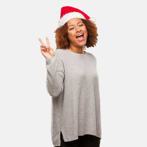 Jovem negra usando um chapéu de papai noel, fazendo um gesto de vitória Foto Premium