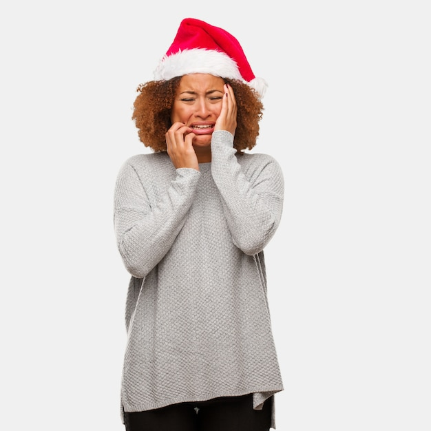 Jovem negra vestindo um chapéu de papai noel desesperado e triste Foto Premium