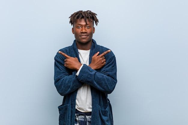 Jovem negro africano vestindo pijama aponta para o lado, está tentando escolher entre duas opções. Foto Premium