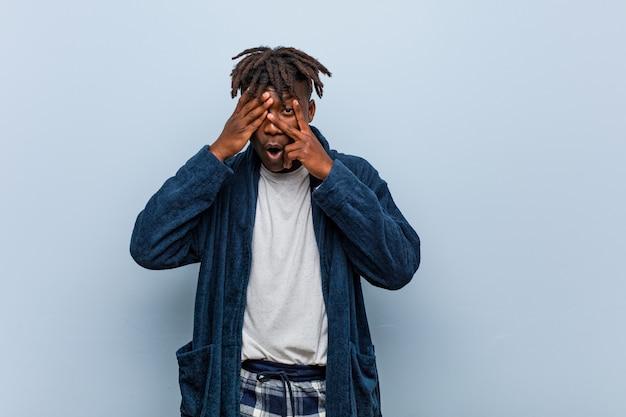 Jovem negro africano vestindo pijama piscar entre os dedos, assustado e nervoso. Foto Premium