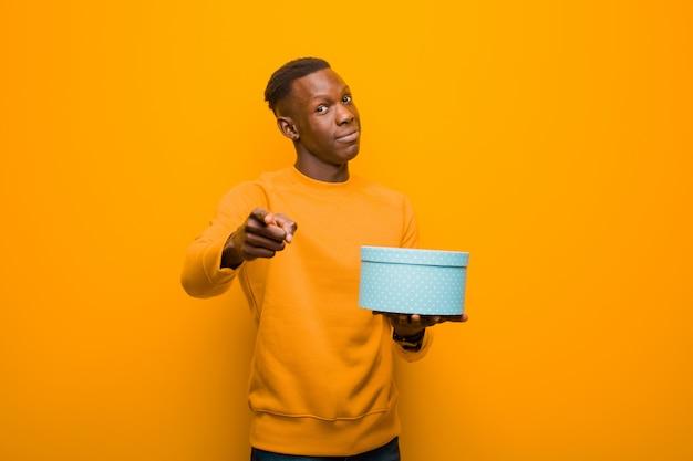 Jovem negro americano africano contra parede laranja com um presente Foto Premium
