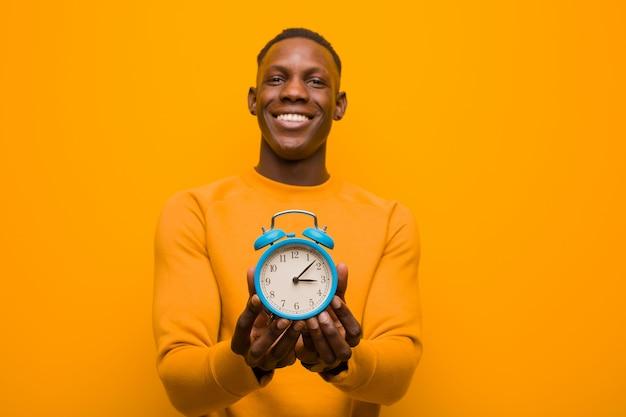Jovem negro americano africano contra parede laranja segurando um despertador Foto Premium