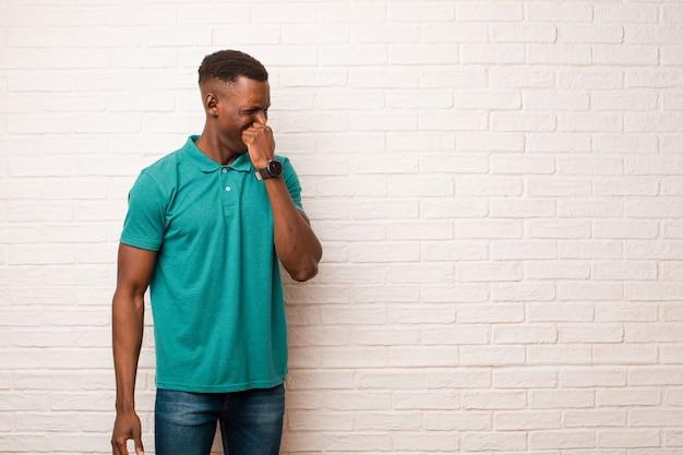 Jovem negro americano africano, sentindo nojo, segurando o nariz para evitar cheirar um fedor sujo e desagradável contra a parede de tijolos Foto Premium