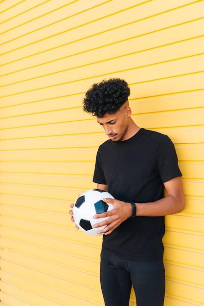 Jovem negro com bola de futebol, abaixando a cabeça Foto gratuita
