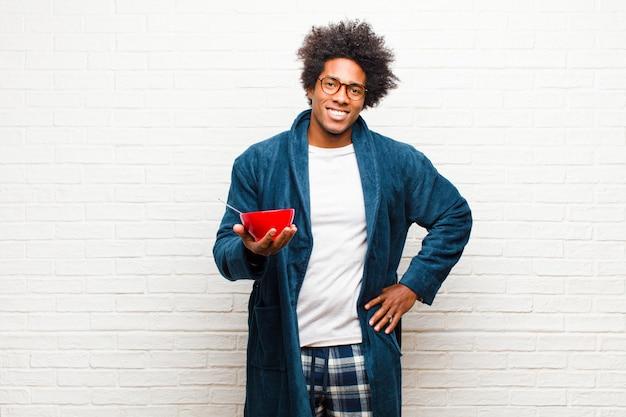 Jovem negro de pijama com uma tigela de café da manhã Foto Premium