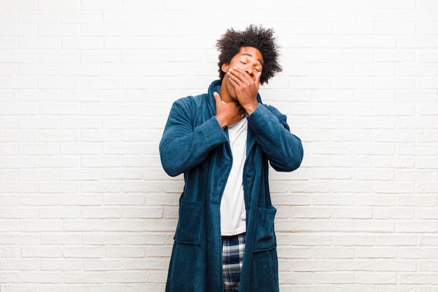 Jovem negro de pijama com vestido sentindo-se mal com sintomas de dor de garganta e gripe, tossindo com a boca coberta contra a parede de tijolos Foto Premium