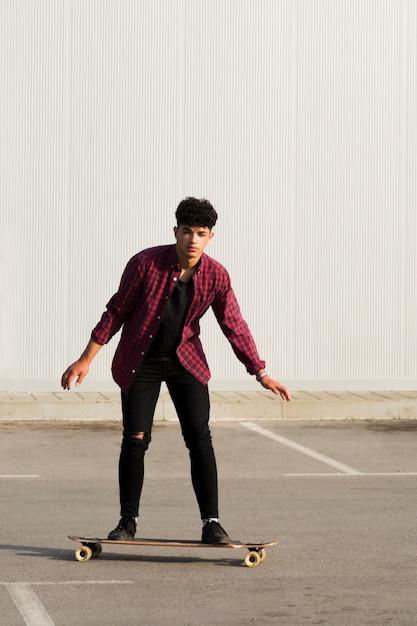 Jovem negro em skate preto de andar de denim Foto gratuita
