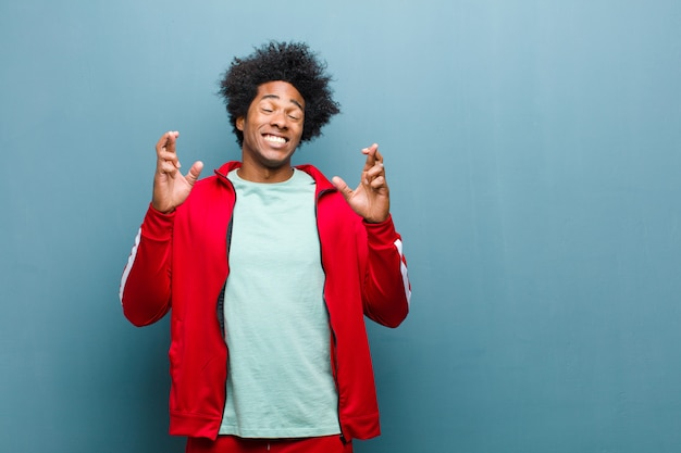 Jovem negro esportes se sentindo nervoso e esperançoso, cruzando os dedos, rezando e esperando a boa sorte contra a parede do grunge Foto Premium