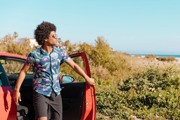 Jovem negro saindo do carro na natureza Foto gratuita