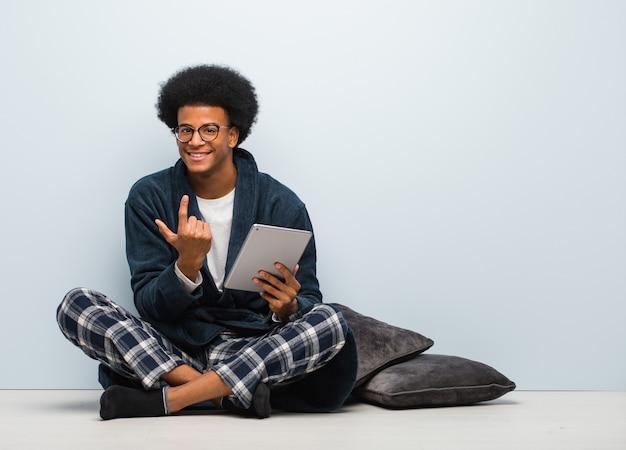 Jovem negro sentado em sua casa e segurando seu tablet convidando para vir Foto Premium