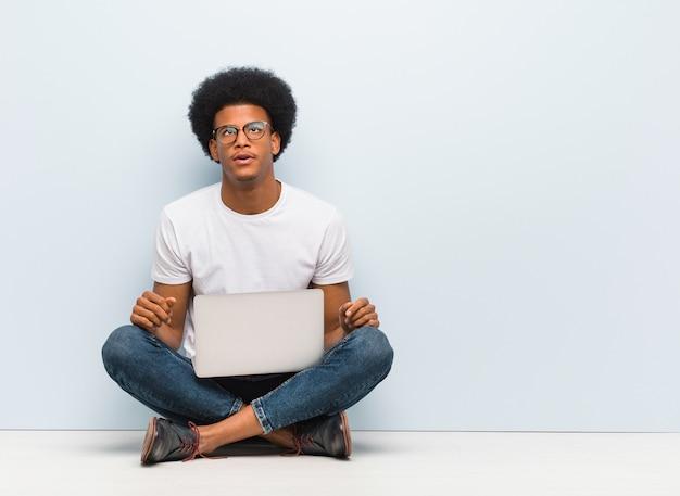 Jovem negro sentado no chão com um laptop cansado e entediado Foto Premium