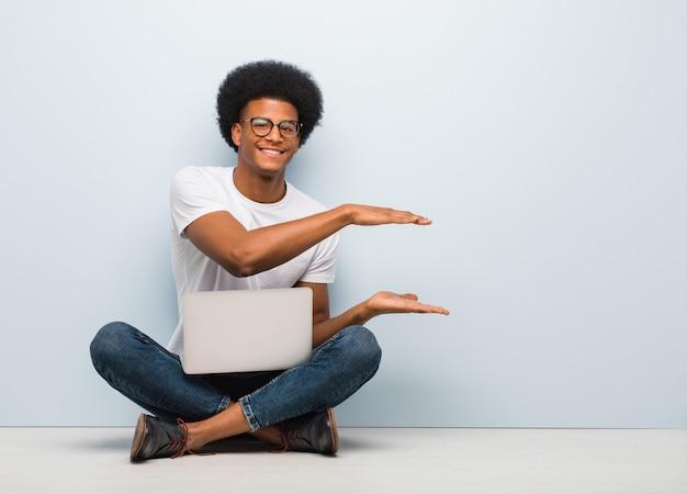 Jovem negro sentado no chão com um laptop segurando algo muito surpreso e chocado Foto Premium