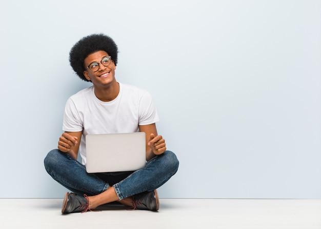 Jovem negro sentado no chão com um laptop sonhando em alcançar objetivos e propósitos Foto Premium