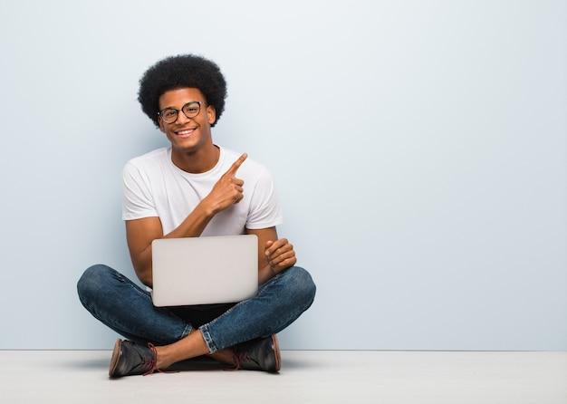 Jovem negro sentado no chão com um laptop sorrindo e apontando para o lado Foto Premium