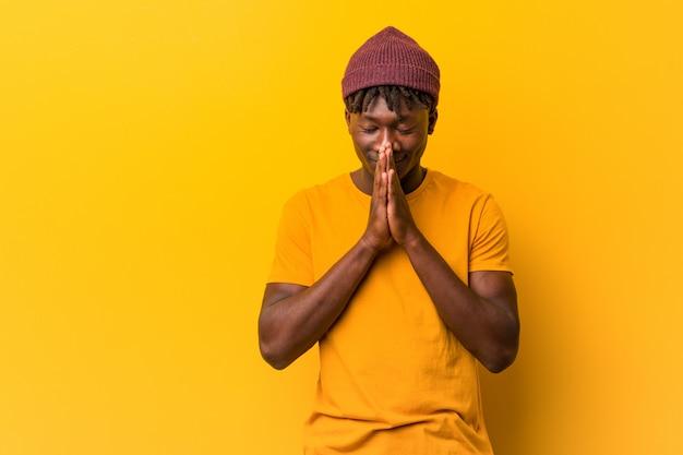 Jovem negro vestindo dreads segurando as mãos em rezar perto da boca, sente-se confiante. Foto Premium