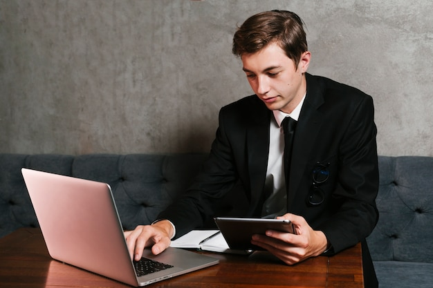 Jovem no escritório trabalhando no laptop Foto gratuita