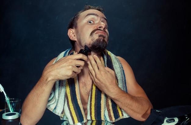 Jovem no quarto, sentado na frente do espelho, coçando a barba Foto gratuita