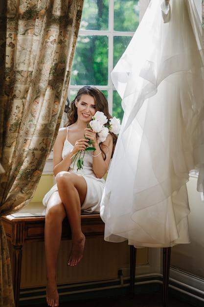 Jovem noiva detém um bouuqet de peônias localização no peitoril da janela na manhã brilhante Foto gratuita
