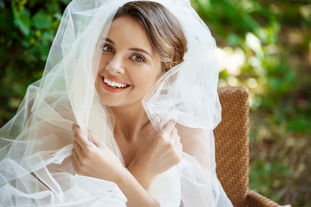 Jovem noiva loira linda no vestido de casamento e véu sorrindo. Foto gratuita